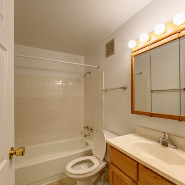Rosewood Apartments - Full-size Bathroom with wooden style cabinet